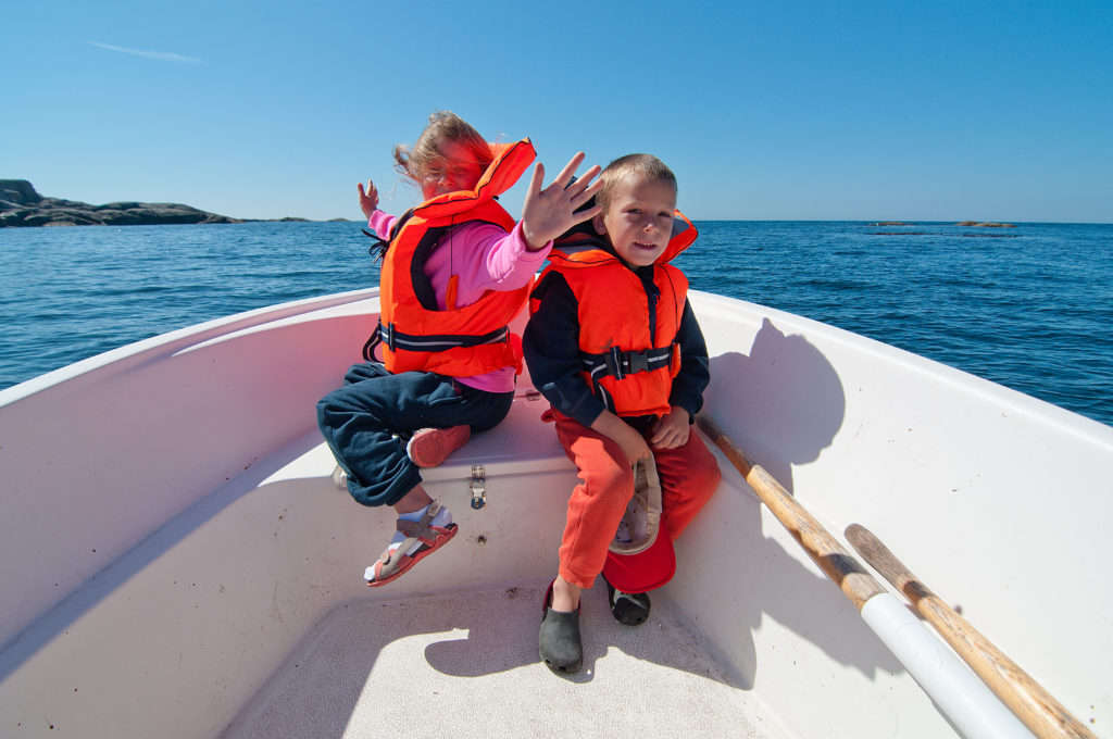 Girl and boy sitting on the prow of the floating boat